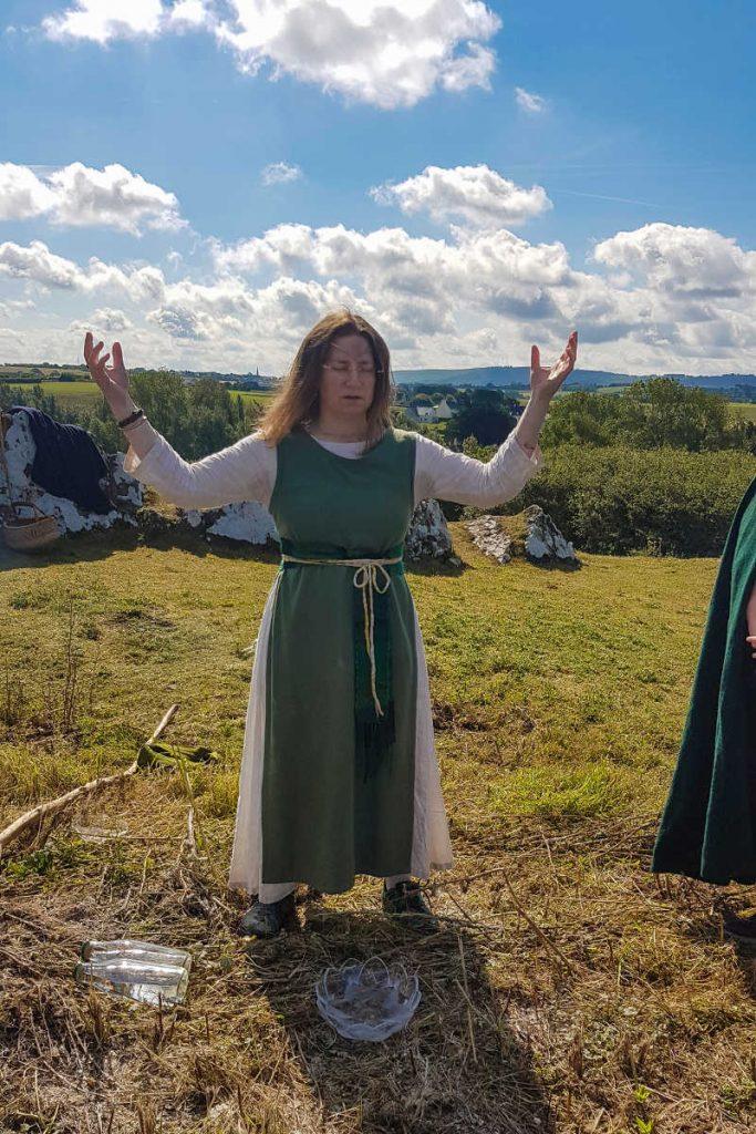 Invocation par Yavanna durant la fête de Dahut, bras levés et yeux fermés.