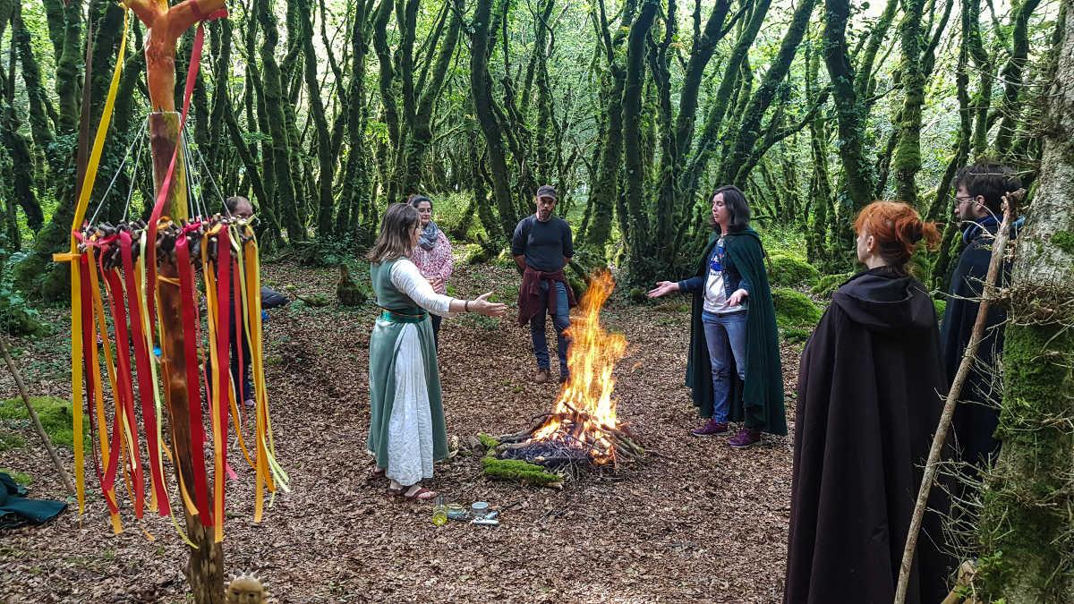 On voit une clairière avec au centre un feu généreux, deux ovates qui officient et des invités qui assistent à la cérémonie du solstice d'été pour célébrer Belenos.