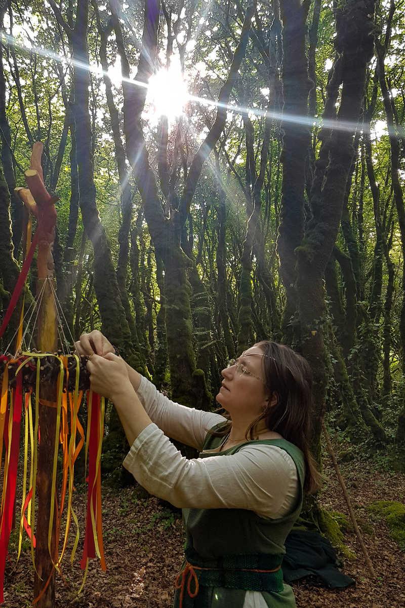 solstice d'été : on voit l'ovate accrocher un ruban sur la couronne du mât de Belenos. Le soleil illumine les frondaisons des arbres des bois de Neved et darde de beaux rayons en étoile.