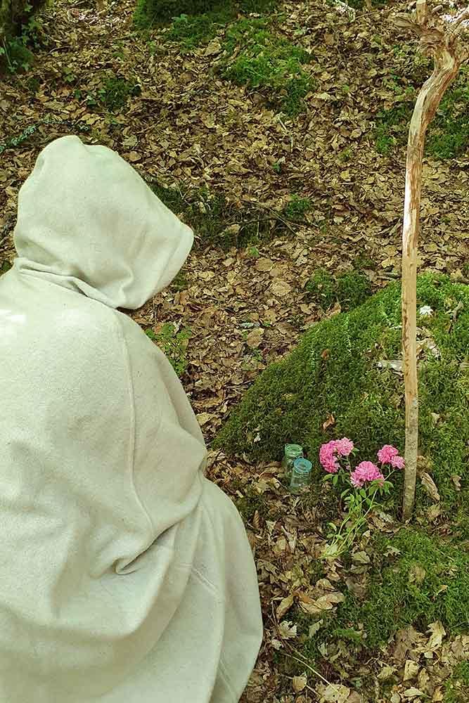 Il y a un druide agenouillé et blotti dans sa saie devant un autel naturel dédié à la Déesse Mélia dont c'est l'un des rite et célébrations druidiques de la saison claire de la Roue 5.