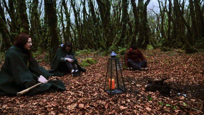 Clairière dans les bois de Neved avec des personnes rassemblées pour méditer autour de bougies omniales.