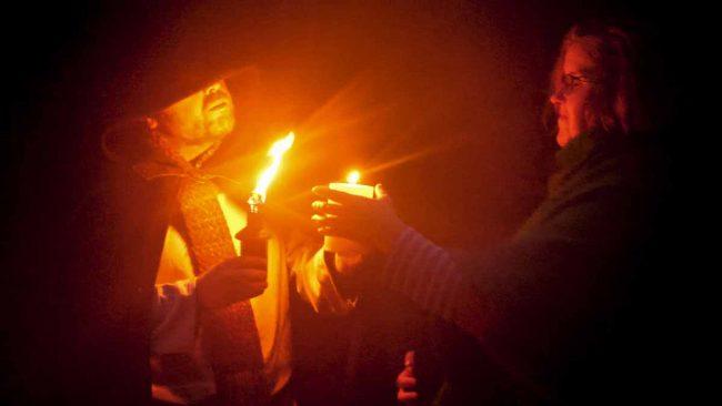 Fête de la Désincarnation : le prêtre du Cornu tend la flamme de Cernunnos à une fidèle.